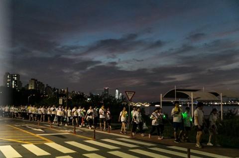 한강의 야경과 함께 걷고 있는 참가자들