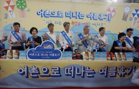 수협중앙회와 해양수산부가 함께하는 여름휴가 어촌에서 보내기 캠페인에서 수협중앙회 임원 및 관계자들이 어촌여행 안내 책자와 수산물 기념품을 시민들에게 나눠주고 있다