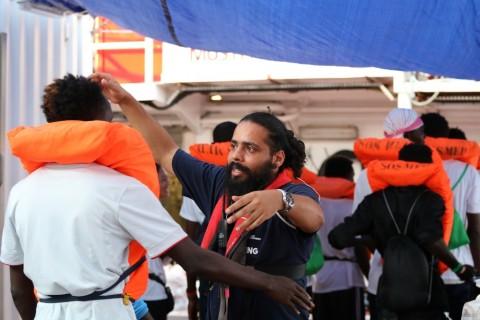 국경없는의사회 직원이 몰타에 하선하기 전 몰타 군 선박으로 이동하는 생존자를 포옹하며 인사하고 있다