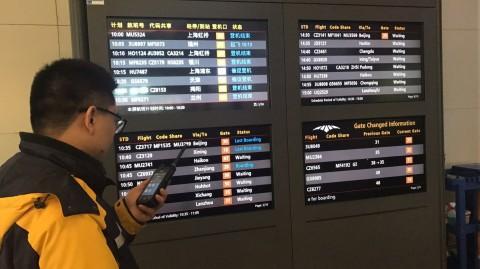 창사 황화국제공항 직원이 다중모드 첨단 무선기기에 설치된 앱을 사용하여 항공편을 확인하고 있다