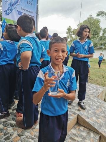 태국의 사캐오 지방의 한 어린이가 와츠와 플래닛 워터 재단이 1000명의 사람들에게 매일 1만리터의 깨끗한 물을 공급하는 정수 필터 타워를 건설한 후 물 한잔을 즐기고 있다