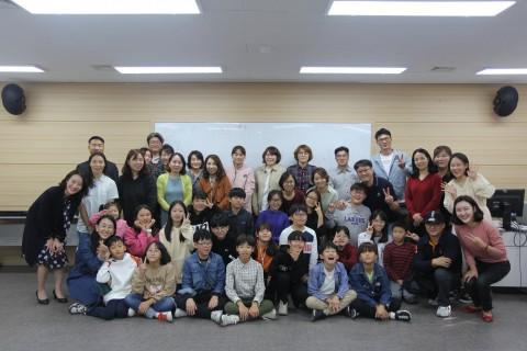시흥꿈나무 세계속으로! 해외견학체험단 성과발표회에 함께한 참가자와 학부모들이 단체 기념사진을 찍고 있다