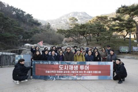도시재생투어에 참가한 시민들이 인왕산을 배경으로 단체기념 촬영을 하고 있다