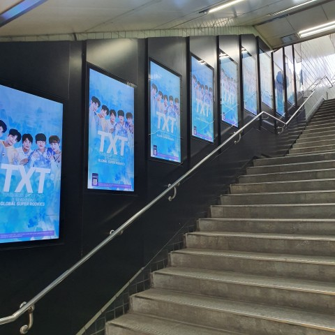 홍대입구역 합정방면 9번 출구 계단에 게재된 TXT의 1주년 축하 광고
