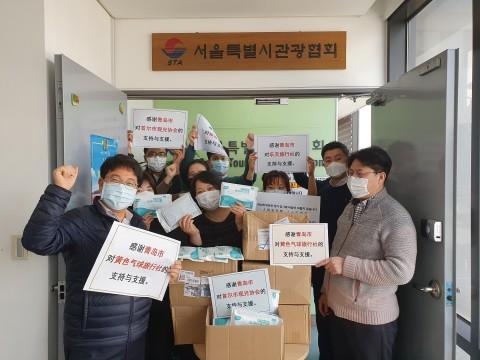 서울시관광협회 직원들이 칭다오시가 기부한 마스크를 받고 기념 촬영을 하고 있다