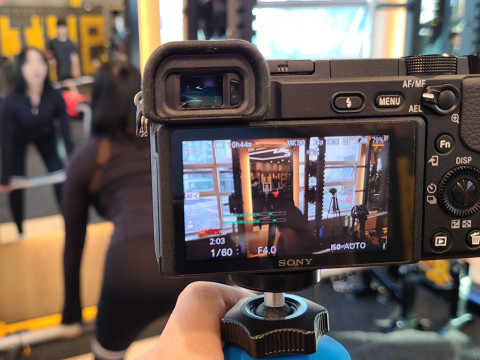 열린의 문성준 PD가 트레이너 모델을 촬영하고 있다. 운동 영상 콘텐츠를 직접 촬영 및 편집해 회원에게 제공하며, 영상은 헬스클럽내 TV모니터와 모바일을 통해 시청할 수 있다