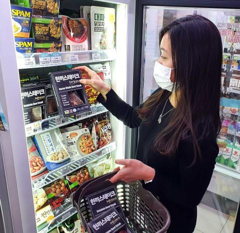 GS25에서 고객이 한끼스테이크 상품을 고르고 있다