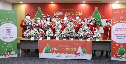 산타복을 입은 교보생명 임직원과 자원봉사자들이 크리스마스 트리를 만든 뒤 기념 촬영을 하고 있다