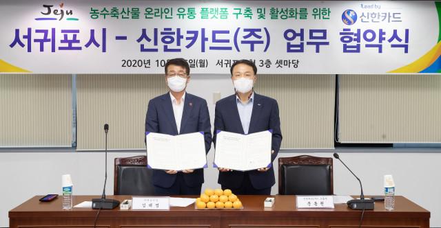 왼쪽부터 김태엽 서귀포시장과 문동권 신한카드 경영기획그룹장이 업무 협약을 체결하고 기념촬영을 하고 있다