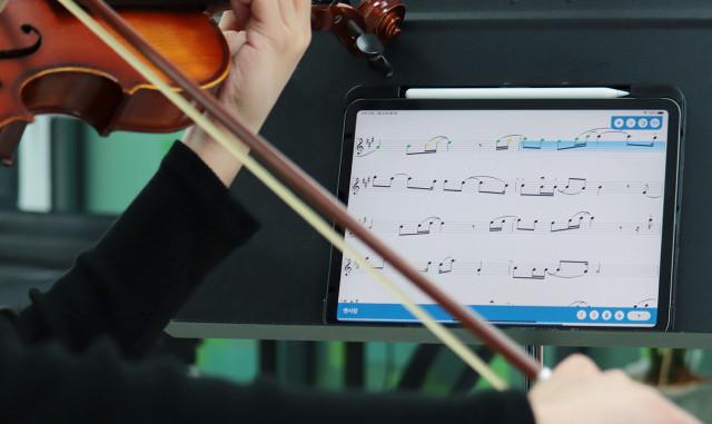 연주자가 수잔스 바이올린 앱으로 바이올린을 켜고 있다