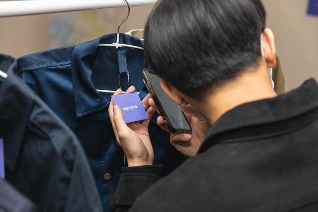 '들리는 옷장'에 참여한 시각 장애인이 솔룩의 애플리케이션을 통해 의류 정보를 듣고 있다