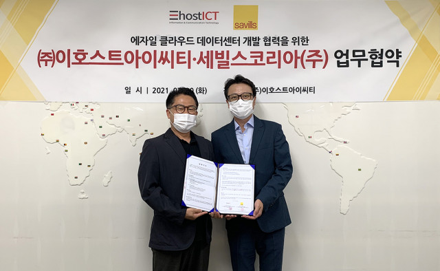 왼쪽부터 김철민 이호스트아이씨티 대표와 최인천 세빌스코리아 전무가 업무협약을 맺고 기념촬영을 하고 있다