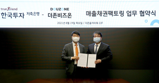 왼쪽부터 권종로 한국투자저축은행 대표, 김용우 더존비즈온 대표가 업무 협약을 맺고 기념 촬영을 하고 있다
